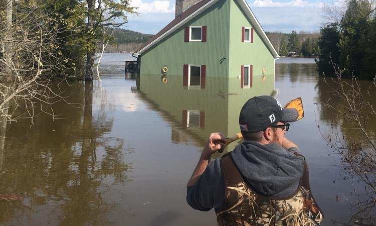 The cottage of John and Sheila Fitzpatrick on Kennebecasis Island has fallen victim to the record-setting flood. Here, John Fitzpatrick Jr. surveys the damage on Sunday. Photo: Courtesy of John Fitzpatrick Sr.